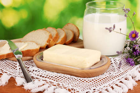 Butter on wooden holder surrounded by bread and milk on natural background Stock Photo - 17001442