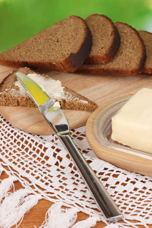 Butter on wooden holder surrounded by bread and milk on natural background close-up photo
