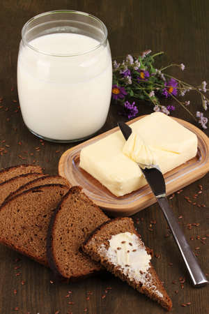 Butter on wooden holder surrounded by bread and milk on wooden table close-up Stock Photo - 17001543