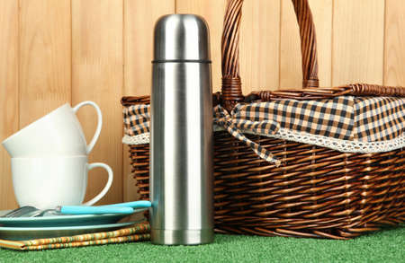 metal thermos with cups, plates and basket on grass on wooden background photo