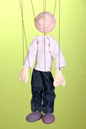 Wooden puppet on green background photo