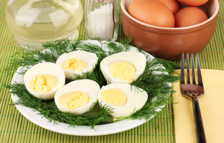 boiled eggs on plate on green background photo
