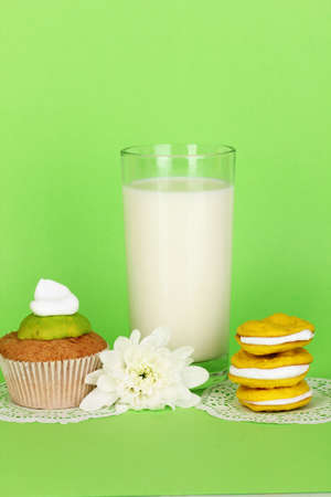 Glass of fresh new milk with cakes on green background photo