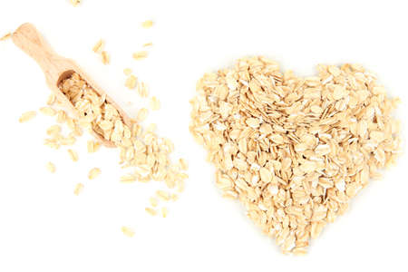 Heart shape made from oat flakes with wooden scoop isolated on white photo
