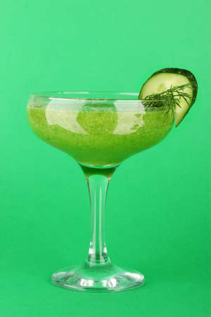Green vegetable juice in coctail glass on green background photo