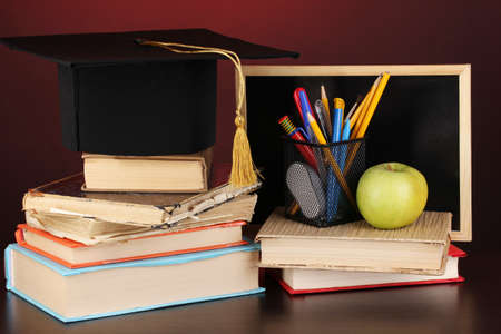 Books and magister cap against school board on wooden table on red background photo