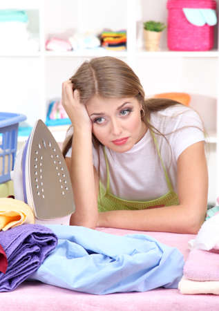 Young girl tired ironing in room photo