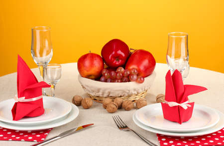 Table setting in red tones on color  background photo