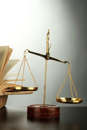 Gold scales of justice and books on grey background photo