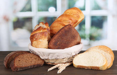 Fresh bread in basket on wooden table on window background Stock Photo - 17001483