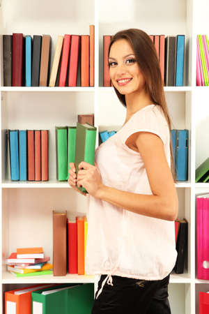 Female student selecting book from library shelf photo