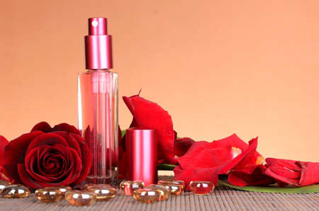 Women's perfume in beautiful bottle with rose on brown background photo