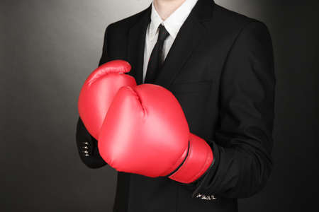 Businessman in boxing gloves on grey background photo