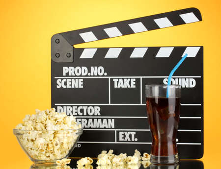 Movie clapperboard, cola and popcorn on orange background photo