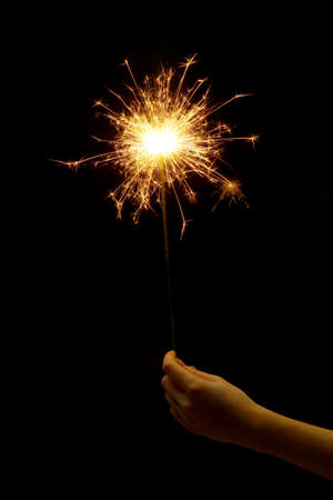 beautiful sparkler in woman hand on black background  photo
