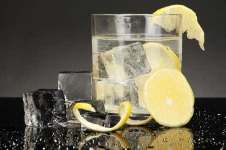Ice cubes in glass with lemon isolated on black Stock Photo - 17001479