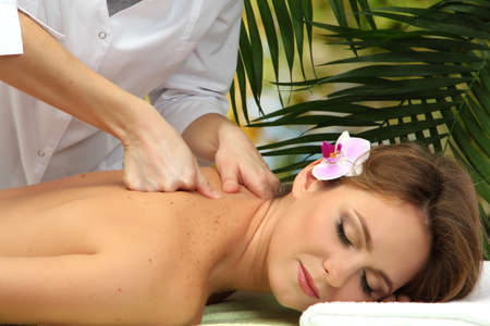 beautiful woman in spa salon  getting massage, on palm leaves background Stock Photo - 17282392