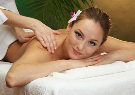 beautiful young woman in spa salon getting massage, on green background photo