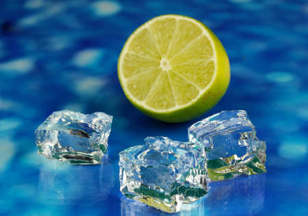 Ice cubes with lime on blue background photo