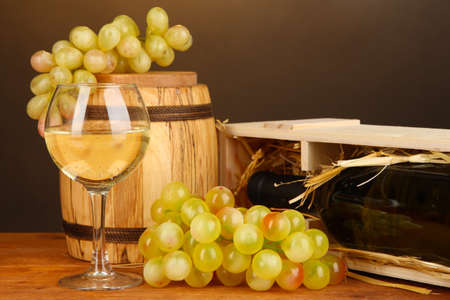 Wooden case with wine bottle, barrel, wineglass and grape on wooden table on brown background Stock Photo - 17001331