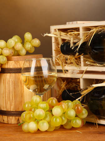 bordeau: Wooden case with wine bottle, barrel, wineglass and grape on wooden table on brown background