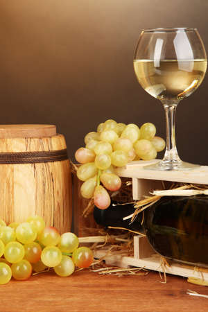 Wooden case with wine bottle, barrel, wineglass and grape on wooden table on brown background Stock Photo - 17001403