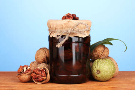 jam-jar of walnuts on wooden table on blue background photo