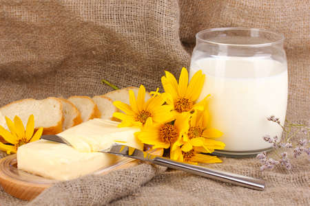 Butter on wooden holder surrounded by bread and milk on sacking background Stock Photo - 17036867