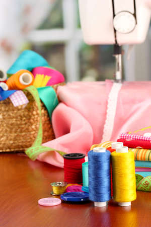 sewing machine and fabric on bright background photo