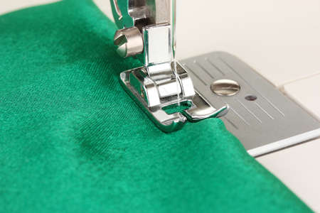 Closeup of sewing machine working part with  green cloth photo