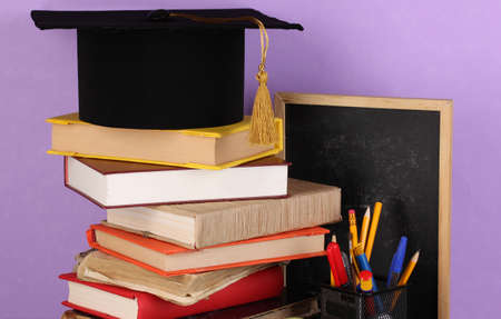 Books and magister cap against school board on wooden table on purple background photo