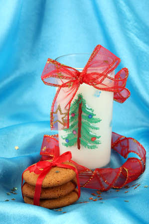 Cookies for Santa: Conceptual image of ginger cookies, milk and christmas decoration on blue background Stock Photo - 17038238