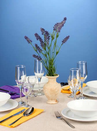 Table setting in violet and yellow tones on color  background photo
