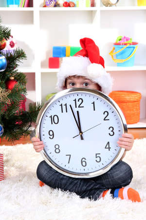 Child with clock in anticipation of New Year photo