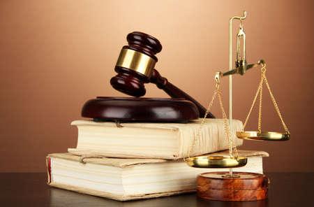 Scale d'oro della giustizia, martello e libri su sfondo marrone