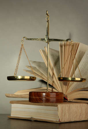 Gold scales of justice and books on grey background Stock Photo