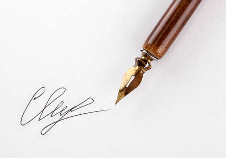 Closeup of signature (fake, not real) and ink pen, isolated on white photo