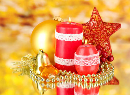 Red candle with christmas decoration on bright background photo