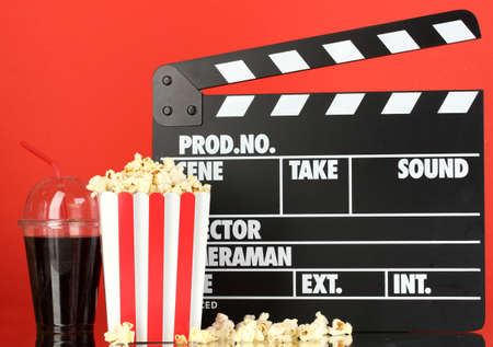 Movie clapperboard, cola and popcorn on red background photo