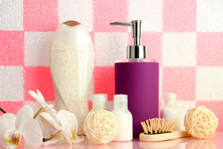 Bath accessories on shelf in bathroom on pink tile wall background photo