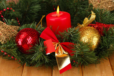 Christmas composition  with candle and decorations in red and gold colors on wooden background Stock Photo - 17038283