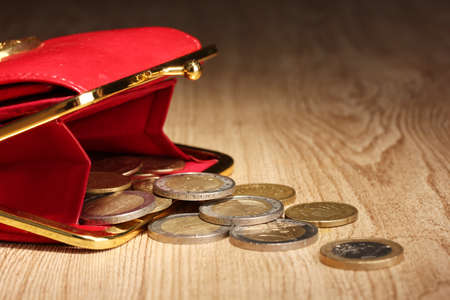takings: female red wallet with coins on wooden background Stock Photo