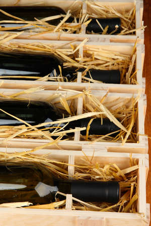 Wooden case with wine bottles close up photo