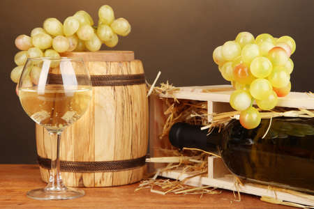 Wooden case with wine bottle, barrel, wineglass and grape on wooden table on brown background Stock Photo - 17038056
