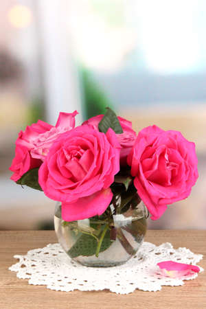 Beautiful pink roses in vase on wooden table on room background Stock Photo - 17037978