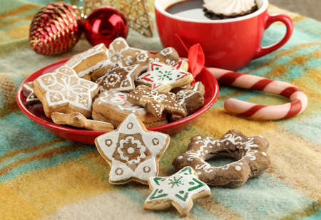 Christmas treats on plate and cup of coffe on plaid close-up photo