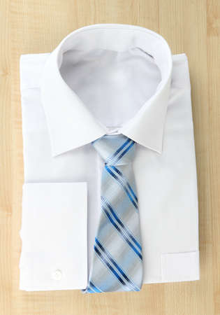 mans shirt: New white mans shirt with color tie on wooden background