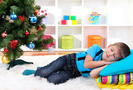 Little boy sleeping under Christmas Tree waiting for Santa Claus to come photo