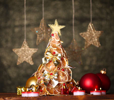 beautiful christmas tree of dry lemons with decor, on grey background photo
