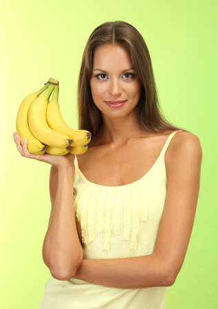 beautiful young woman with bananas, on green background photo